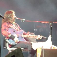 Dave Grohl elevates his broken foot on stage right after getting injured.