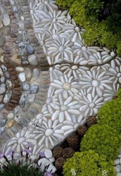 The flora in this beautiful garden extends beyond the planting beds into the pebble mosaic path that contains them.