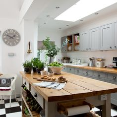 Shaker meets modern family kitchen-diner. Give a country kitchen a modern edge by introducing a monochrome checkered floor. A combination of white, grey and taupe is a classic colour combination for a traditional kitchen and looks smart against rustic wooden worktops. Clock, Newgate Clocks, Similar island John Lewis of Hungerford.