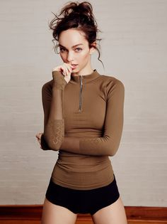 Slay Top   American made in our Signature Seamless fabric, this long sleeve performance top features a super stretchy feel with a mock neck and a half-zip detail. Sleeves have subtle cutouts that create cute accents with thumbholes to keep them in place while you move.