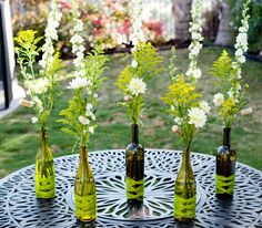 wine bottle arrangements -- would be perfect for an outdoor dinner party under some twinkling lights