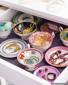 Jewelry storage with mismatched teacups... Notice earrings hanging around sides of the cup...
