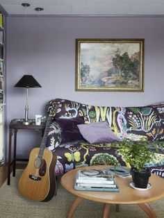 Purple Living Room    An Anthropologie sofa, upholstered in Josef Frank fabric, and a Heywood-Wakefield coffee table furnish this living room, painted in Behr's Elm Bark.