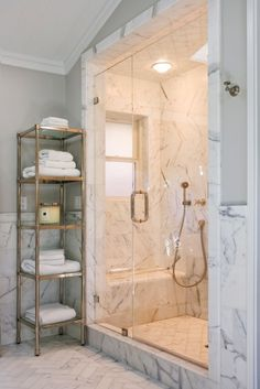 Marble tile on floor, half way up walls, in shower and around shower