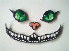 Cheshire cat in four perler bead-pieces. In lack of black I had to use some kind of silver beads.