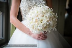 Bride with her white dress holding a white ivory rose and dendrobium orchid bridal bouquet.