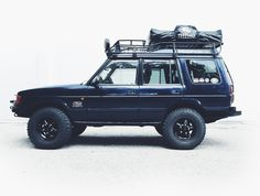 "The Overland Empire adventuremobile. 1999 Land Rover Discovery Series 1. BajaRack EXP roof rack, Treeline Outdoors rooftop tent, original Land Rover auxiliary lights, BF Goodrich mud terrain tires, Old Man Emu 2"" lift, Defender steering components, custom front bumper and sliders, RTE Fabrication rear bumper, and Warn 8274 winch with Viking synthetic line. Ready for any adventure we throw at it."