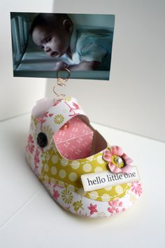 cute paper baby shoe: what about using as place card holders-what if we spray paint little clothes pins and cut out Cricut owls-attach them and put a magnet on the back and use during the shower, but guests use as fridge magnets after?