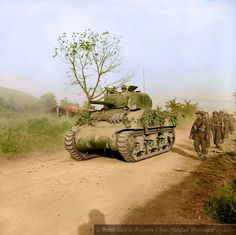 Guardsmen from the 3rd Battalion Welsh Guards are passed by a Sherman tank of the 26th Armoured Brigade, 6th Armoured Division as they move forward on Route 6 to attack Monte Piccolo outside Arce, Lazio, Italy. 27th of May 1944.