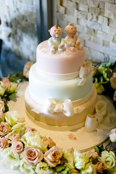 Nefeli & Dimitri's christening cake. Two little twins atop a cake decorated in soft hues and wrapped with sugar bows to celebrate their christening. Chocolate fudge cake and white chocolate mud cake