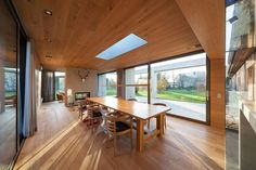 DIning room draped in wood with skylight and unabated view of the green scenery…