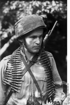 German paratrooper in the Netherlands in 1944 with rifle and ammo MG belt.