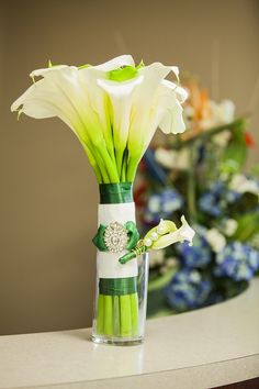 Hand tied bridal bouquet featuring white and dark green calla lily wrapped with emerald green and white ribbons. Calla Lily Bridal Bouquet, Calla Lily Flowers, Floral Bouquets, Calla Lilies, White Ribbon, Gold Wedding, Glass Vase, Wedding Decorations, Boutonnieres