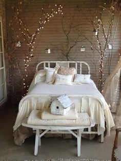 LOVE this bedroom! Brick walls, lighted branches as a backdrop, white iron bed…