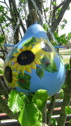 Sunflower Sunshine .... We have cleaned and cut this gourd for a birdhouse...then we base coated it with a Blue Jay Blue. To that we painted a birdhouse full of Sunshine Yellow With A Touch Of Orange Bright Sunflowers surrounding this gourd.. Thats not All we added a few Ladybugs