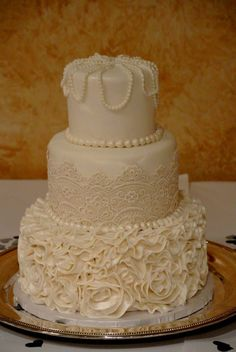 Actual photo of my vintage inspired wedding cake with rosettes, lace, and pearls placed on an antique silver tray.