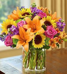 Guaranteed to deliver an impression! This unique floral arrangement is brimming with bright, colorful and cheery garden favorites like sunflowers, lilies, and roses artfully designed in a chic glass vase. Perfect for any occasion - celebrate a...