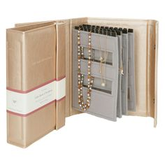 A clever storage idea for necklaces with four pages to keep necklaces secure and tangle free. Secures with two poppers. The book contains four pages and a handy information page is included to show the various ways you can secure your necklaces. Gold faux leather with grey inner pages. A great gift idea with a practical purpose.