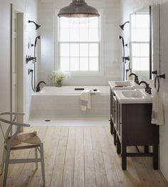 salle de bains vintage avec carrealge blanc, plancher en bois et douches