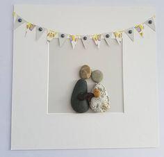 A beautiful and unique handmade pebble art picture of couple holding baby, with lovely yellow and grey bunting. This picture is a lovely home decoration and would also make a perfect gift for new parents / christening. The picture is made using pebbles, card and silver pearls. All materials are carefully placed and fixed with high strength glue onto high quality owl grey card. I can include printed quotes or personalised messages onto picture. I can also add people / children to th...