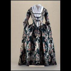 Robe à la francaise, remodeled à l'anglaise, England, 1730s, remodeled c. 1750. Green silk brocaded with blue, red, and orange flowers, and a lacy background pattern of white.