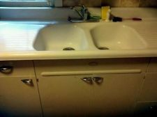 Double drainboard sink with double sinks and 4 inch backsplash with deck mounted faucet with metal cabinet. Found on ebay.