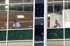 People look out from office building windows as snow falls in downtown Philadelphia, Jan.