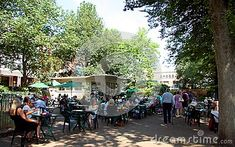 People sitting at tables in the sunshine at the Royal Pavilion cafe in the gardens in Brighton.