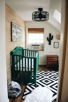 Cactus Themed Boy's Nursery in black and white with emerald green crib. Ikea rug and wood accent wall.