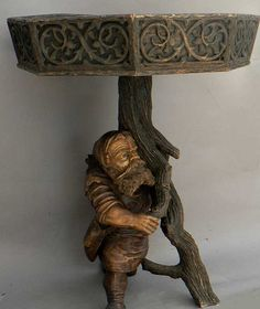 a black forest carved wood dwarf plant stand.