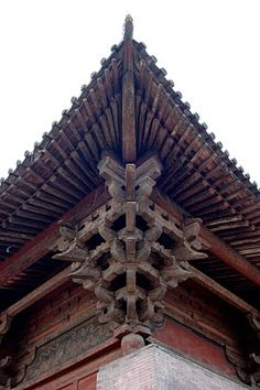 Close of of the complex bracketing system (dougong) often found in traditional Chinese Architecture.  Similar to flying buttresses, in addition to being decorative, they have an important structural function in helping to support and extend the size of the heavy tile roofs and distributing the weight more evenly onto the vertical column, since walls (with their large door/windows and thin latticework) in traditional Chinese building, were usually non-load-bearing.