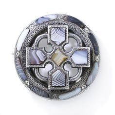 This study in gray and white agate, with a touch of butterscotch in the center, measures just over 1 and 3/4 inch in diameter. A stylized Celtic cross overlays a circle pin in this very cool nineteenth-century Scottish kilt pin. Victorian
