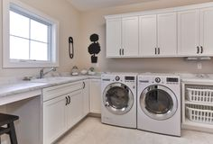 Geneva Cabinet Company Lake Geneva, WI Laundry with white cabinets for storage and organization with open shelving for laundry bins #cabinets #storage #laundry #organization