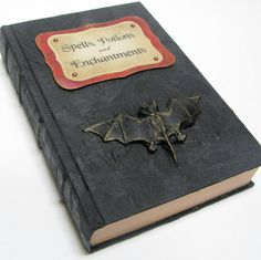 "A Book of Dark Spells: Grab an old hardcover book, and cover it with black construction paper. Use card stock or construction paper to craft a spooky label highlighting the book's magical contents. For a finishing touch, find a small bat or spider ""talisman"" at the dime store, and glue it to the cover. Source: Etsy seller ElvesInTheAttic"