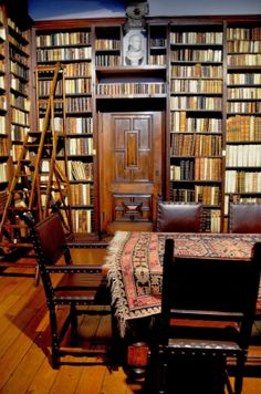 From a Bloomsbury Life, Antwerp library---bookshelves over door and to ceiling of painted clouds on a blue sky, bare board floor and a rug on the table.  A refreshing change from Remodelista Style.