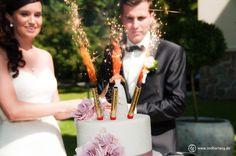 Die #Hochzeitstorte wird aufgefahren. Dahinter das #Brautpaar, sichtlich glücklich und ergriffen. #Hochzeitsbilder vom Profi!