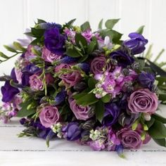 Stunning dark purple lisianthus, cool water lilac roses, scented pink stocks, lilac freesias and purple veronica, finished with dark green ruscus foliage.