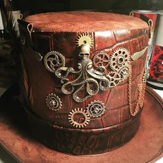 Beautiful chocolate brown Mens #Steampunk top hat. Suede and alligator leather are combined on the base. This hat has brass and gold gold steampunk findings adorned with chains with the Kraken as a focal point a throwback to Jules Vern. This hat has a working pocket watch tucked into its own leather pouch. Feathers add a touch of whimsy to the hat. This one is classy yet fun! A personal favorite from my Etsy shop http://etsy.me/2jQbVUk