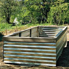 raised beds made from corrugated metal and posts from a chainlink fence - possible recycling idea for the posts from our busted, ugly old chainlink!
