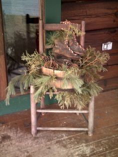 antique ladder back chair and antique skates with wooden bucket and greenery sitting on my front porch