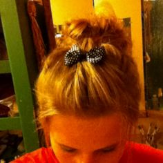 High messy bun with bangs pinned back in a bow. Cute and very easy and fast to do How to- Gather hair in a ponytail put ponytail holder around as many times needed , then on the last time only pull half way take remaining hair & twist until u form a messy bun bobby pin & comb ur bangs and twist & pin !Easy!