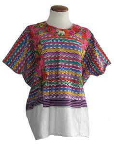 This 30-year-old huipil comes from Quetzaltenango (Xela), Guatemala and was handwoven on a backstrap loom. It features multi-colored, Ikat-dyed striped patterns over a white background of rayon/cotton, with silk floral embroidery and a little lamb on the collar. See more at: www.elinterior.com