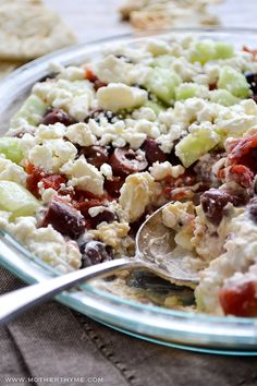 An easy recipe for Layered Greek Dip with creamy hummus and topped with Tzatziki, feta, cucumbers, tomatoes and olives. Serve with pita chips or flatbread.