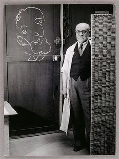 Henri Matisse standing against a screen and drawing with chalk, 1939.