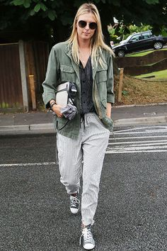 Tennis star Maria Sharapova was snapped headed to Day 5 of Wimbledon on June looking ready to watch – not play – a few sets. In a casual outfit, Sharapova wore seersucker trousers, a striped button up top, and distressed army jacket with grey accessories. Army Jacket Outfits, Maria Sharapova Hot, Maria Sarapova, Tennis Players Female, Tennis Fashion, Comfy Pants, Tennis Clothes, Great Women, Seersucker