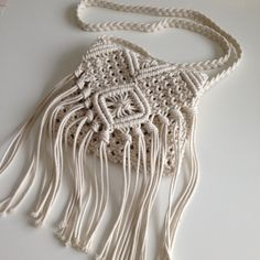 Please allow 2 to 3 weeks to produce this bag. Thanks Crossbody macrame handbag with fringe 7 inch made with natural cotton interior lined with zip, flap bag  mesurement are approx :: 8 x 8 inch (without fringe) strap mesure 47 inch  made in non-smoked and no-pet house  also see little crossbody bag crochet : https://www.etsy.com/fr/listing/267617992/sac-main-bandouillere-avec-frange?ref=shop_home_listings