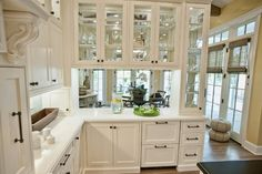 Glass-front peninsula cabinets. Some kitchens have a peninsula that divides the cooking space and another adjacent space (often the dining room). Peninsulas are accessible on three sides. Although peninsula storage is practical, many homeowners feel that it can close the kitchen off. Adding upper glass-front cabinets to the peninsula allows for light and creates a more open feeling.
