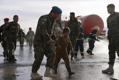 Afganistanin armeijan upseeri talutti lievästi loukkaantunutta poikaa itsemurhaiskun jälkeen maanantaina Mazar-i-Sharifin seudulla Afganistanissa.
