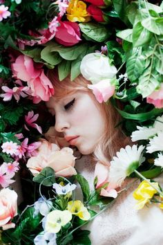 dreamy girl with cat eye makeup sleeps in bed of ethereal colorful flowers of pink peach yellow green and blue