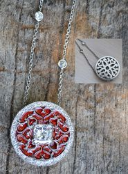 Platinum diamond and red enamel pendant on diamond chain.